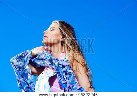 Beautiful dreamy girl looking into the distance over blue sky. Summer style. Holidays. Beauty, fashion.