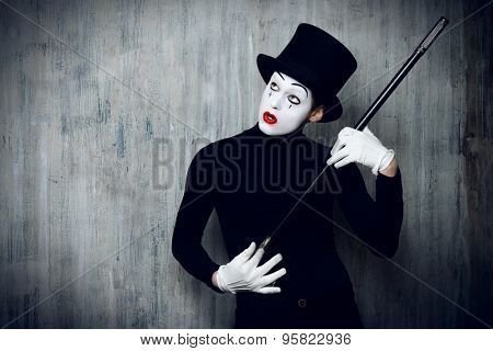 Elegant expressive male mime artist posing with walking stick by a grunge wall.