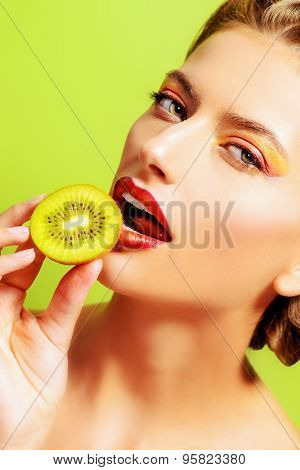 Beautiful sexy young woman eating kiwi over green background. Tropical fruits. Healthy eating. Beauty, cosmetics.