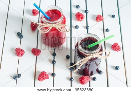 Raspberry, strawberry jam and blueberry, blackberry marmalade in glass mason jar, with fresh berries