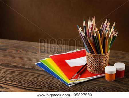 Pencils, paints and brushes on wooden table .