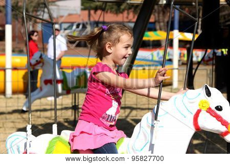 Sweet Little Girl Riding On Carousel Festival