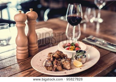 Grilled pork ribs with salad, lemon, sauce and the glass of red wine