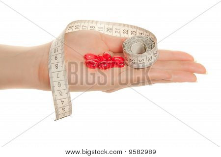 Woman's Hand With  Red Pills And Tape Measure