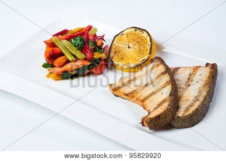 grilled fish steak with lemon and vegetables