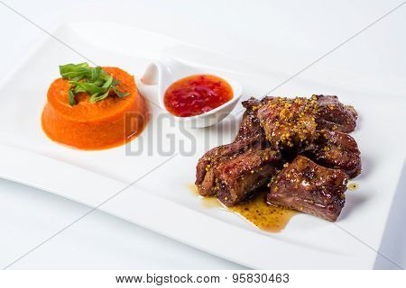 Barbecued pork ribs served with tomato sauce and carrot puree  isolated on white background