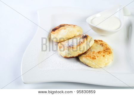 Rustic dessert, cheesecakes on a plate, with sour cream and mint isolated