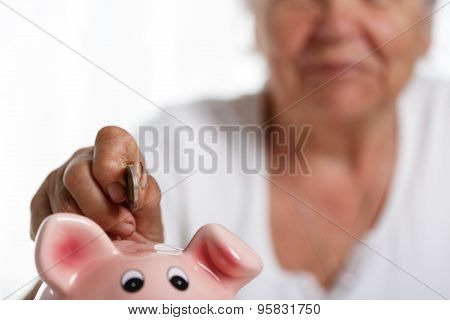 Elder Woman Putting Pin Money Coins Into Pink Piggybank Slot