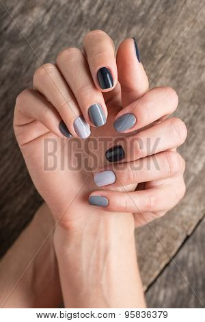 Beautiful hands with the miniature painted in a gray-colored nai
