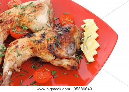 served grilled chicken legs with tomatoes lemon and thyme on red plate isolated on white background