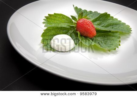A Plate With Strawberry And Cream