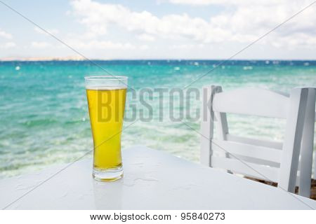glass of beer on a table against the sea