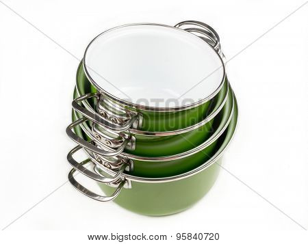 Set of four stacked green enamel pots shot from above on white background