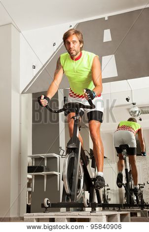 Young attractive male is working out in a cycling gym.