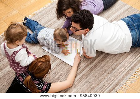 family group of five - two babies and three adults lying on the carpet, drawing a picture together.