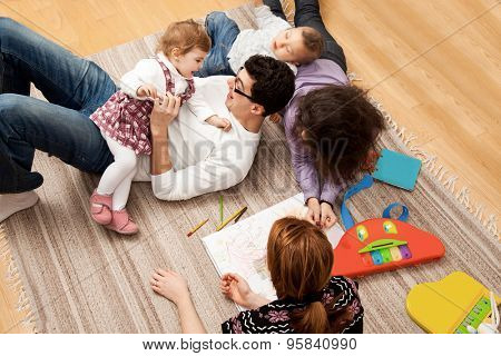 friends or relatives family group of five - two babies and three adults lying on the carpet, dad is tickling his daughter.