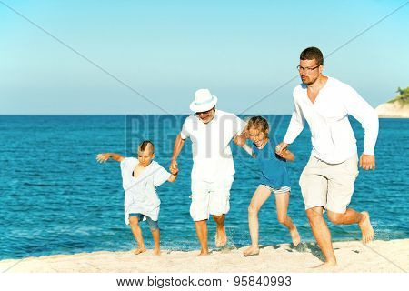Joyful family summer sea vacation of three generations. Grandfather, son, grandson and granddaughter are running hand in hand on the beach.
