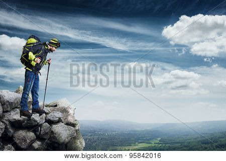 hiker with backpack and hiking poles standing on the top of rock and looking down