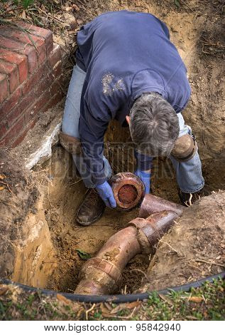 Man Working On Old Clay Ceramic Sewer Line Pipes