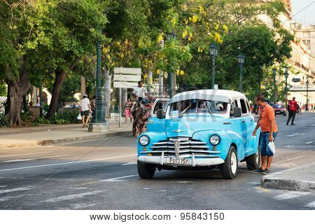 HAVANA,CUBA - JUNE 28, 2015 : A man asks for a ride in an old american car still used as a taxi in Old Havana
