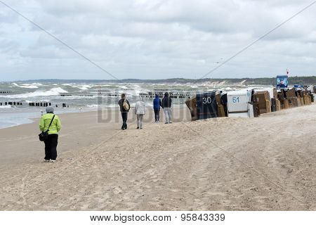USTKA - JULY 10: Tourists walking along the beach on a cold summer day on 10 July 2015 in Ustka, Poland.