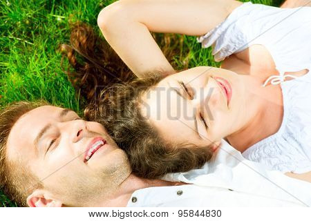 Happy Smiling Couple Relaxing on Green Grass. Park. Young Family Lying on Grass Outdoor. Happiness, relationships concept