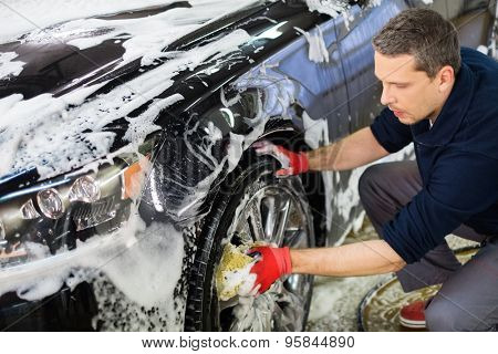 Man worker washing car's alloy wheels on a car wash