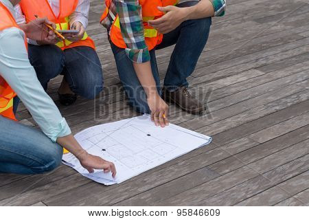Engineers discussing plan of the building