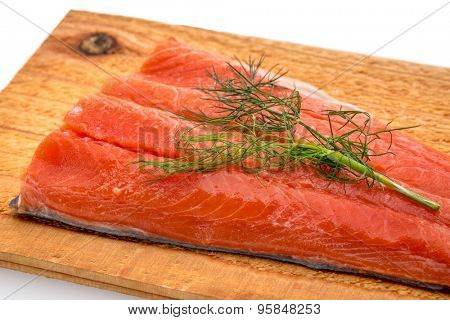 a portion of sockeye salmon prepared for grilling on a water soaked cedar wood plank with green dill