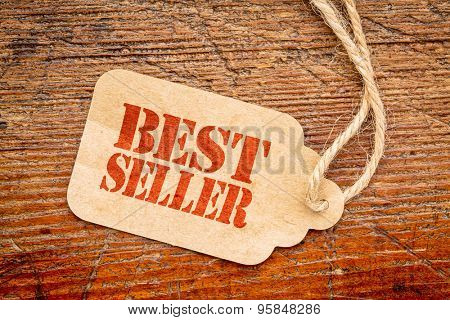 bestseller  sign - a paper price tag against rustic red painted barn wood - shopping concept