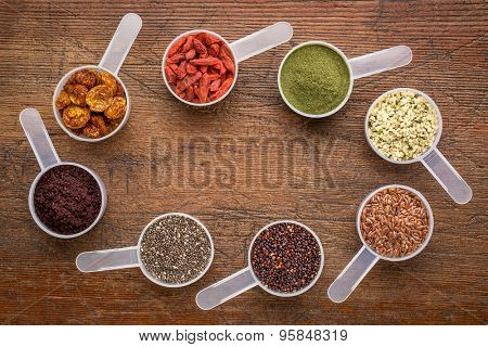superfood abstract (wheatgrass, acai berry, goji berry, flax seed,chia seed,goldenberry,hemp seed, quinoa grain) - top view of measuring scoops surrounding  a copy space on a rustic wood