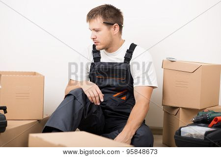 Frustrated Man Sitting Between Brown Carton Boxes