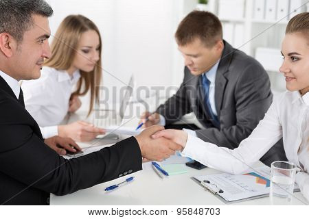 Businessman In Suit Shaking Woman's Hand