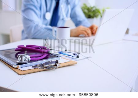 Male doctor using a laptop, sitting at his desk