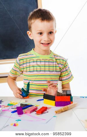 Smiling boy playing with plasticine