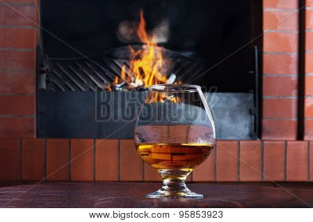 Two Glasses Of Cognac On The Old Brick Fireplace