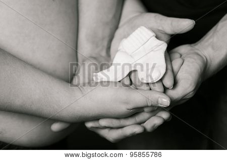 Hands of men and women on pregnant belly with  socks