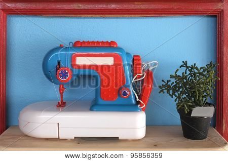 Toy and vintage sewing machine on blue background with pot of plant