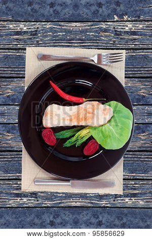 fresh roast turkey meat fillet steak served with vegetables on plate over blue wooden table