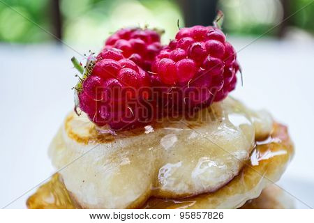 Some pancakes with raspberries and honey, close up
