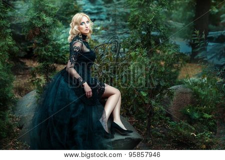 Girl Black Dress Sitting On A Rock In The Forest.