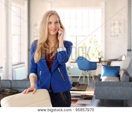 Young blonde woman talking on mobilephone at home.