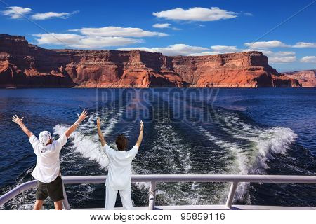 Woman and man in the stern boat delighted nature. Artificial lake Powell on the Colorado River, USA. The lake is surrounded by picturesque beaches of the orange sandstone