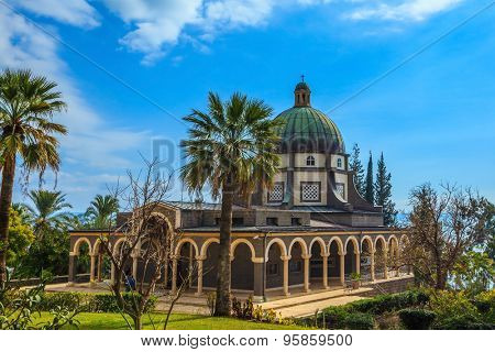 The dome of basilica is surrounded by a gallery with columns. Church Sermon on the Mount - Mount of Beatitudes. Subtle shade of palms and cypresses
