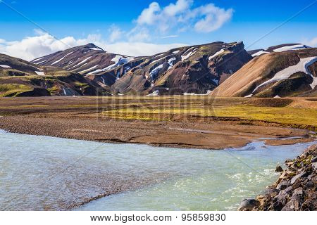 The picturesque valley in the national park Landmannalaugar, Iceland.  Summer flood of meltwater blocks the way to the camping