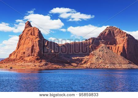 Lake Powell is surrounded by magnificent sandstone hills. Boat trip on sunny day. Scenic huge artificial water basin of the Colorado River, USA
