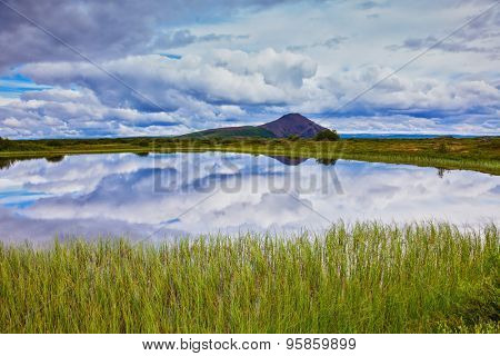 In the smooth water of cold lake reflects cloudy sky. Small lake surrounded by green meadow. Summer Iceland