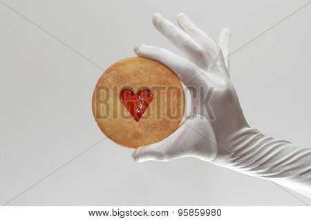 White Woman's Gloves Holding A Cookie With Heart-shaped Jam Isolated On White Background