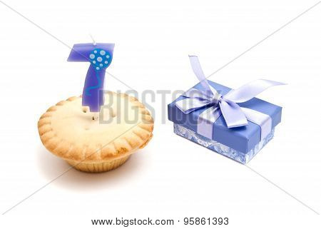 Cupcake With Seven Years Birthday Candle And Gift On White