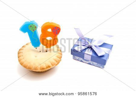 Cupcake With Eighteen Years Birthday Candle And Gift On White